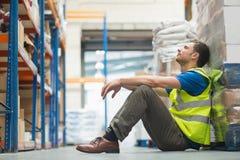 Zmęczony ręcznego pracownika obsiadanie na podłoga obrazy stock