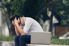 Zmęczony sfrustowany młody Azjatycki biznesowy mężczyzna z laptopem ma kłopot przy outside biurem rocznika stonowany wizerunek obraz royalty free