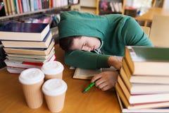 Zmęczony uczeń lub mężczyzna z książkami w bibliotece Obrazy Stock