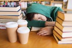 Zmęczony uczeń lub mężczyzna z książkami w bibliotece Obrazy Royalty Free