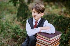 Zmęczony uczniowski obsiadanie na książkach w parkowej pobliskiej szkole Zdjęcia Royalty Free