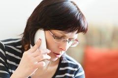 Zmęczony w średnim wieku kobiety wezwanie telefonem obrazy stock