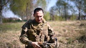 Zmęczony wojownik lub wojskowego żołnierz ubierający w kamuflażu, hełm z gogle, kamizelka kuloodporna zdejmujemy jego hełm i zdjęcie wideo