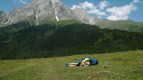 Zmęczony wycieczkowicz z wielkim plecakiem spada ziemia przeciw tłu piękny góra krajobraz, chory mężczyzna obraz royalty free