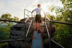 Zmęczony wycieczkowicza utrzymania poręcz na szczycie Pogodny wiosna brzask w skalistych górach Wycieczkowicz z czerwoną baseball Obraz Royalty Free