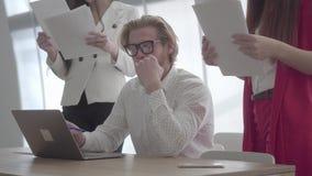 Zmęczony zaakcentowany mężczyzny obsiadanie w wygodnym biurze z netbook przy stołowym podpisywaniem który żeńscy koledzy dokument zbiory wideo