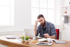 Zmęczony zaakcentowany męski programista z laptopem w nowożytnym białym biurze Zdjęcie Royalty Free