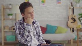Zmęczony zanudzający młody Azjatycki mężczyzna obezwładniający w wózku inwalidzkim w domu zbiory wideo
