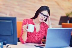 Zmęczony zapracowany bizneswoman przy biurowym nakryciem jej twarz z rękami Fotografia Royalty Free