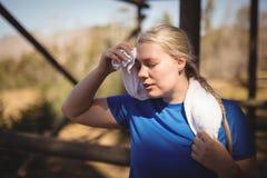 Zmęczony kobiety obcierania pot po treningu podczas przeszkoda kursu Zdjęcie Stock