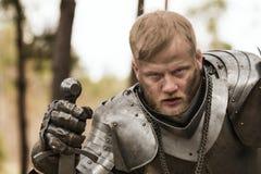 Zmęczony rycerz w zbroi po bitwy na lasowym tle Zdjęcie Royalty Free