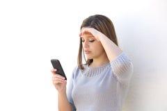 Zmartwiona kobieta patrzeje telefon komórkowego Obrazy Royalty Free