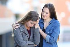 Zmartwiona kobieta pociesza jej smutnego przyjaciela w ulicie obraz stock