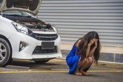 Zmartwiona kobieta potrzebuje remontowej usługi i pomocy w stresie splatał na poboczu z samochodową awarią silniką ma mechanika p zdjęcie royalty free