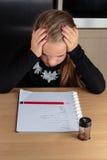 Zmartwiona młoda dziewczyna robi pracie domowej przy kuchennym stołem obraz royalty free