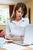 Zmartwiona W Średnim Wieku kobieta Patrzeje gospodarstwo domowe finanse zdjęcia royalty free
