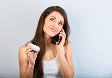 Zmartwiona zmieszana młodej kobiety mienia pastylki butelka w wzywać pytać lekarkę telefonie komórkowym i ręce Jest przyglądająca zdjęcia stock