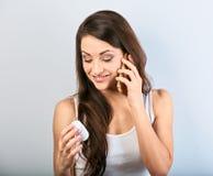 Zmartwiona zmieszana młodej kobiety mienia pastylki butelka w wzywać pytać lekarkę telefonie komórkowym i ręce Jest przyglądająca obrazy stock
