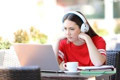 Zmartwioni studenccy nauczania online dopatrywania tutorials na laptopie obrazy stock