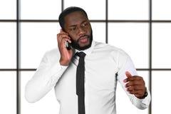 Zmartwiony afro facet z telefonem komórkowym Obrazy Stock
