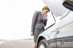 Zmartwiony bizneswoman patrzeje awaria samochód na drodze przeciw niebu fotografia stock