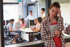 Zmartwiony Żeńskiego ucznia czekanie Na zewnątrz szkoły wyższa Tutorial Zdjęcia Stock