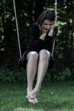Zmartwiony kobiety obsiadanie na huśtawce Zdjęcia Royalty Free