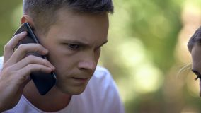 Zmartwiony młody człowiek dzwoni 911 donosić przestępstwo lub pytać dla medycznej pomocy, zbliżenie obrazy royalty free