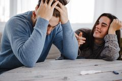 Zmartwiony mężczyzna i szczęśliwa kobieta z ciążowym testem zdjęcia royalty free