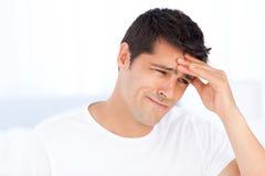 Zmartwiony mężczyzna ma migrenę w jego sypialni zdjęcia stock