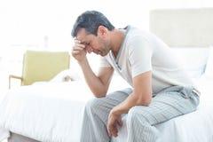 Zmartwiony mężczyzna obsiadanie na łóżku obrazy royalty free