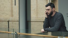 Zmartwiony mężczyzna opowiada na jego Smartphone w sala zbiory wideo