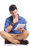 Zmartwiony młody przypadkowy mężczyzna czytanie na pastylce Obrazy Royalty Free