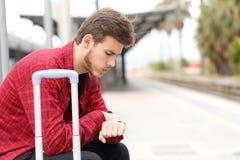 Zmartwiony podróżnika czekanie dla opóźniającego pociągu zdjęcia stock