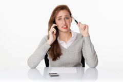 Zmartwiony 20s biznesowej kobiety główkowanie na telefonie w białym biurze Obrazy Stock
