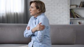 Zmartwiony starszy żeński obsiadanie na leżance, czuje niespokojnych, psychologicznych problemy, obraz stock