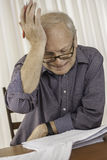 Zmartwiony starszy biznesmen lub nauczyciel pracuje przy jego biurem Zdjęcie Royalty Free