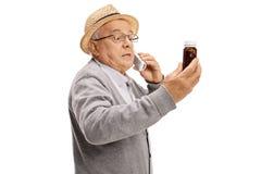 Zmartwiony starszy opowiadać na telefonie i trzymać butelkę pigułki obraz stock