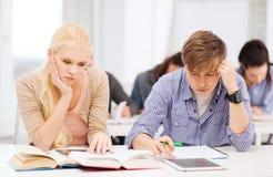 Zmęczeni ucznie z komputerem osobistym, notatnikami i książkami pastylki, Zdjęcie Stock