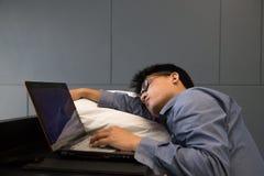 Zmęczony Azjatycki biznesmena dosypianie na laptopie z poduszką Zdjęcia Royalty Free