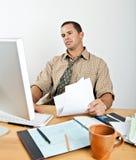 Zmęczony młody człowiek przy biurko Płaci rachunkami Zdjęcia Royalty Free