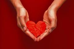 Zmięty czerwień papieru serce w rękach na czerwonym tle Zdjęcia Royalty Free