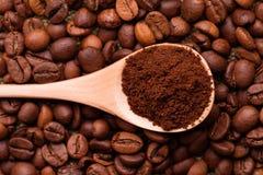 Zmielona kawa w łyżce na tle całe kawowe fasole zdjęcia royalty free