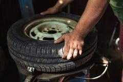 Zmienia opon?, Samochodowy mechanik Zmienia opon? w gara?u fotografia royalty free