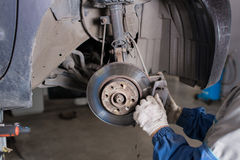 Zmienia starą przejażdżkę Brandnew hamulcowy dysk na samochodzie w garażu Auto mechanika naprawianie Fotografia Stock