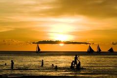 Zmierzch i żeglowanie łodzie na biel plaży Fotografia Royalty Free