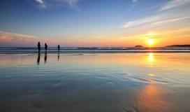 Zmierzch i sylwetki przy plażą Obrazy Royalty Free