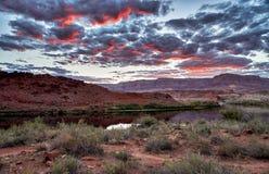 Zmierzch jest rozjarzony w chmurach nad Kolorado rzecznymi i Vermillion falezami obraz royalty free