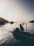 Zmierzch jezioro i sylwetka mężczyzna i motorowa łódź Fotografia Stock