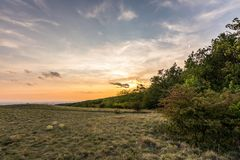 Zmierzch krajobrazowa panorama, wzgórza w złotej godzinie, mała wioska w dolinie, piękni kolory i chmury, Zdjęcia Royalty Free